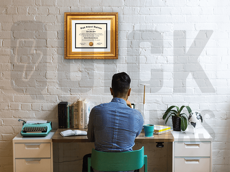 young man sitting in teal chair at desk with high school diploma in gold frame hanging on brick wall